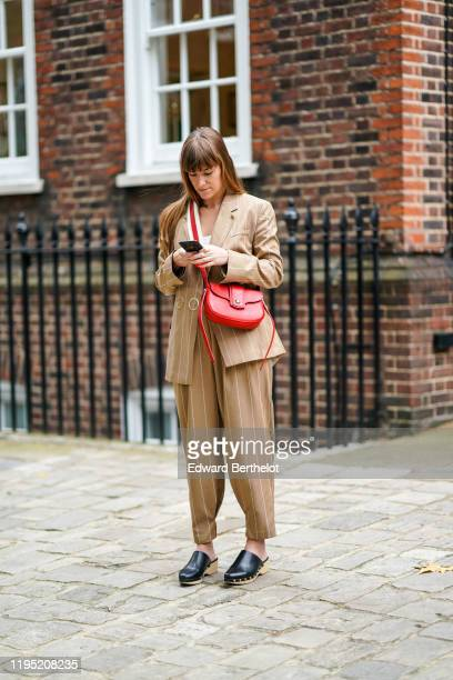 A guest wears a light brown striped blazer jacket a red shoulder strapped leather bag cropped pants black leather sandals outside JW Anderson during...
