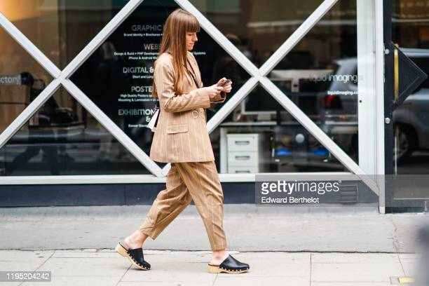 A guest wears a light brown striped blazer jacket cropped pants black leather sandals outside JW Anderson during London Fashion Week September 2019...