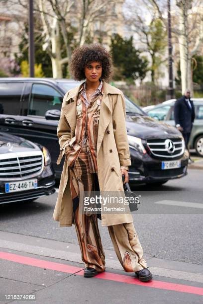 Guest wears a light brown trench coat, a black bag, a brown and beige pyjama striped shirt, flare pants, leather shoes, outside Leonard Paris, during...