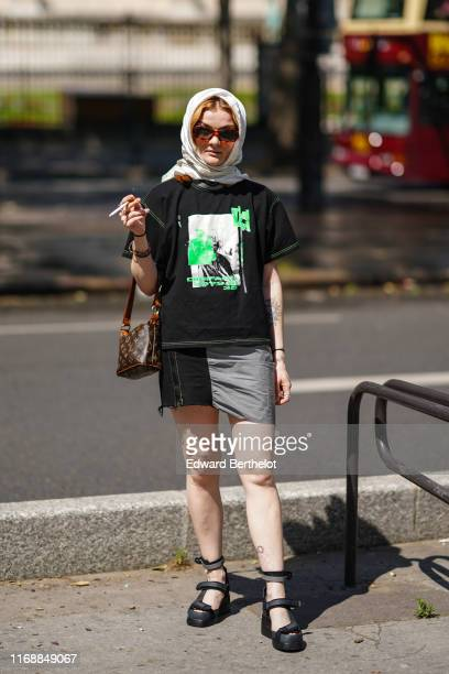 A guest wears a light grey hair scarf sunglasses a Louis Vuitton monogram bag a black tshirt with green apparent stitches and green prints a ripped...