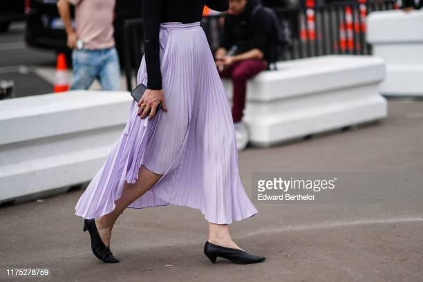 Guest wears a light purple asymmetric pleated skirt, pointy black kitten heeled pumps, outside Acne Studios, during Paris Fashion Week - Menswear...