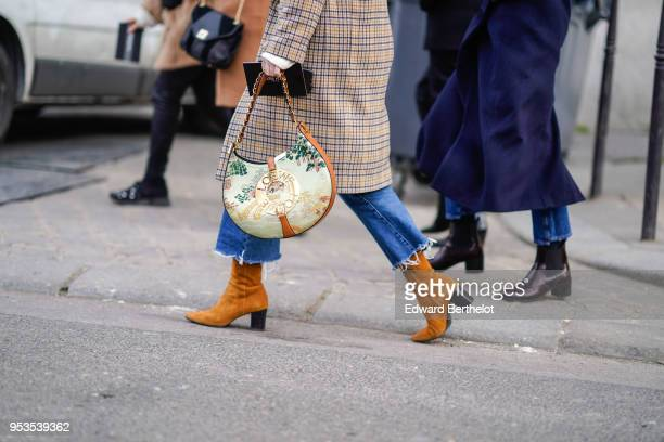 A guest wears a Loewe bag brown suede boots blue ripped jeans a tartan checked coat during Paris Fashion Week Womenswear Fall/Winter 2018/2019 on...
