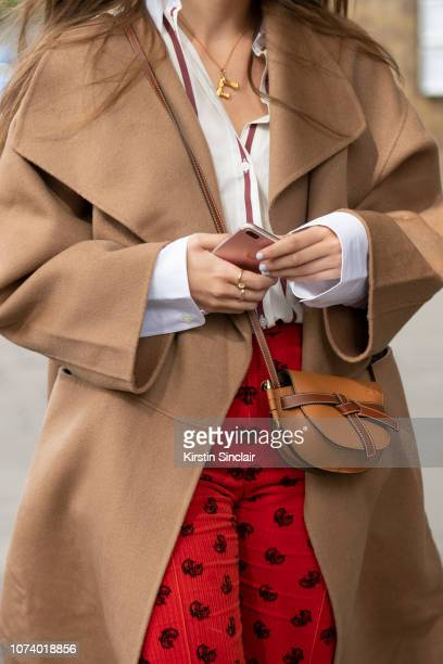 A guest wears a Loewe bag Chloe trousers white shirt and a camel coloured coat during London Fashion Week September 2018 on September 16 2018 in...