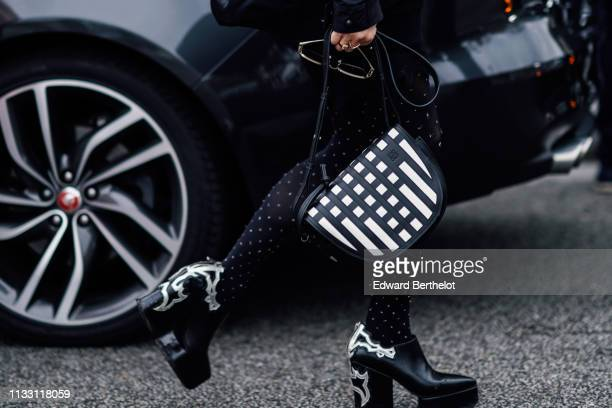 A guest wears a Loewe black and white half moon bag black platform ankle boots with white inserts black tights with white polka dots outside Nina...