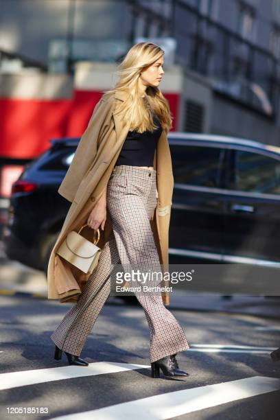 Guest wears a long beige coat, a black top, checkered flare pants, black pointy high heel leather boots, outside Tory Burch, during New York Fashion...