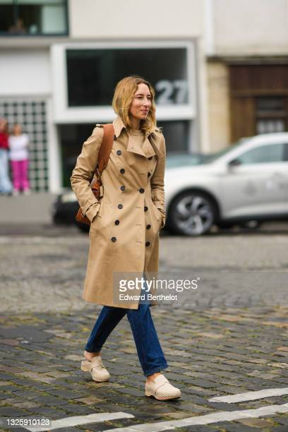Guest wears a long beige trench coat, blue flared denim jeans pants, a camel grained leather Kelly handbag from Hermes, beige nailed / studded mules...