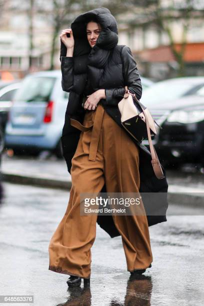 A guest wears a long black puffer jacket with a hood a bag and brown flared pants outside the Celine show during Paris Fashion Week Womenswear...