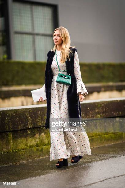 A guest wears a long black sleeveless vest a beige pantsuit with flouncy sleeves and palazzo pants a green crossbody bag black wedges outside...