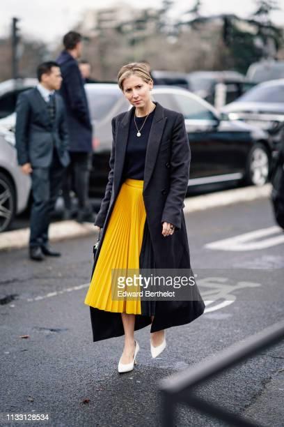 A guest wears a long blazer jacket a black top a necklace a yellow pleated skirt white shoes outside Balmain during Paris Fashion Week Womenswear...