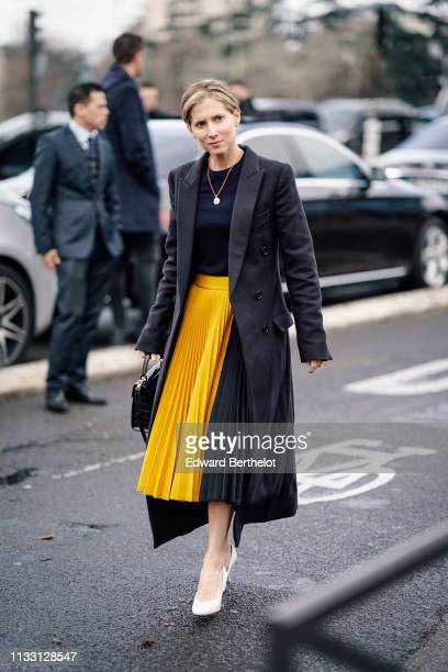 A guest wears a long blazer jacket a black top a necklace a yellow pleated skirt white shoes outside Balmain during Paris Fashion Week Womenswear...