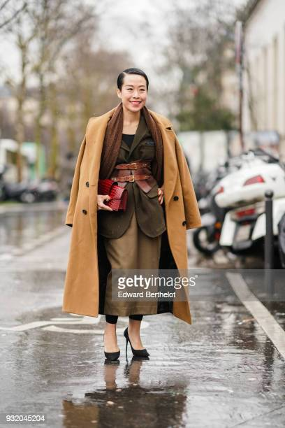 A guest wears a long camel coat a brown scarf a red clutch a khaki jacket a yellow bronze long skirt black leggings black stilettos a red double...
