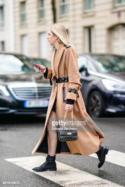 A guest wears a long camel wrap coat with black patent belt and epaulettes black shorts black fishnet tights black ankle boots and a black studded...