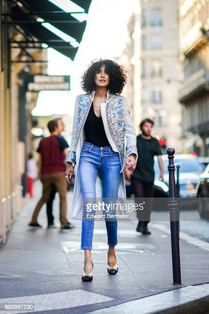 A guest wears a long glitter jacket blue jeans a black low neck top shoes outside Valentino during Paris Fashion Week Haute Couture Fall Winter...