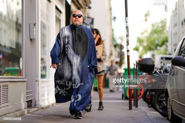 A guest wears a long jacket outside Yohji Yamamoto during Paris Fashion Week Menswear SpringSummer 2019 on June 21 2018 in Paris France