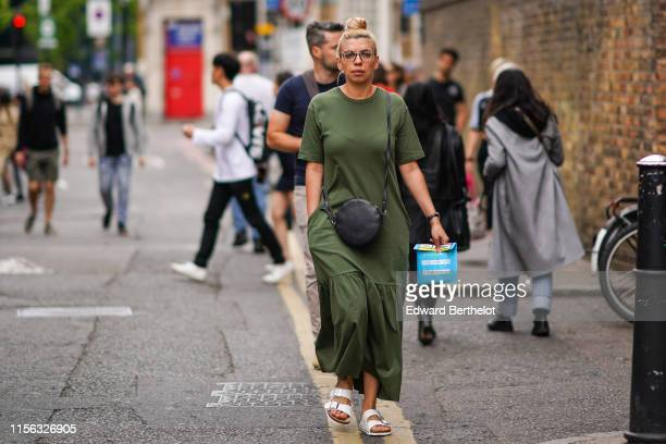A guest wears a long khaki dress a black round canteen bag white beach sandals during London Fashion Week Men's June 2019 on June 09 2019 in London...