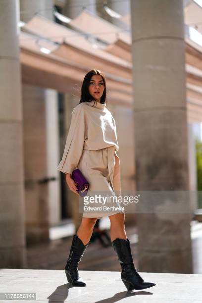 Guest wears a long sleeves cowl collar beige dress, a purple clutch, black snake-skin pointy calf-boots, during Paris Fashion Week - Womenswear...
