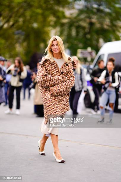 A guest wears a long wool coat with geometric pattern outside Chanel during Paris Fashion Week Womenswear Spring/Summer 2019 on October 2 2018 in...