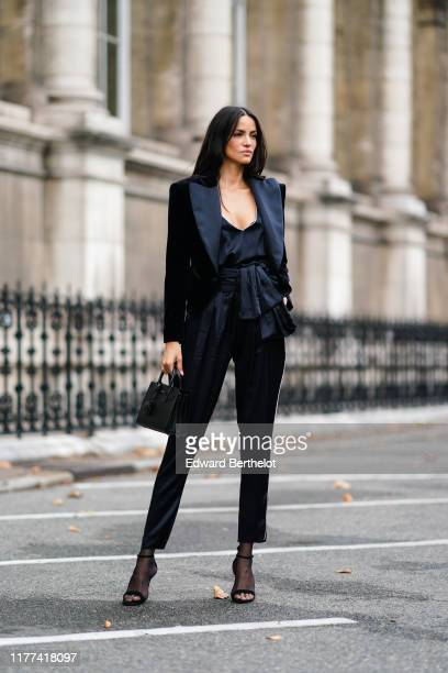 A guest wears a low neck silky top a balck jacket black pants mesh shoes outside Redemption during Paris Fashion Week Womenswear Spring Summer 2020...