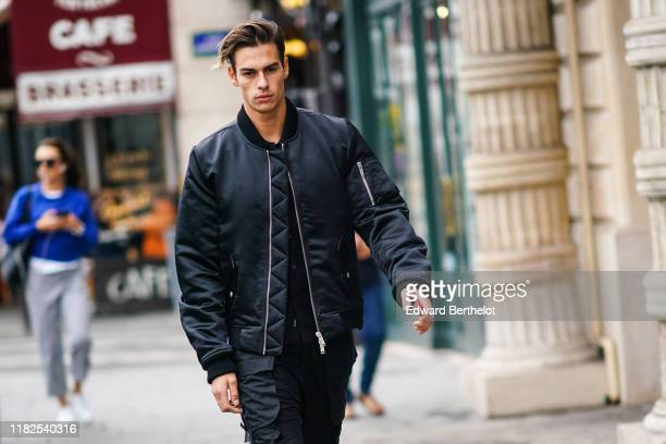 A guest wears a lustrous black bomber jacket black cargo pants outside Unravel Project during Paris Fashion Week Womenswear Spring Summer 2020 on...