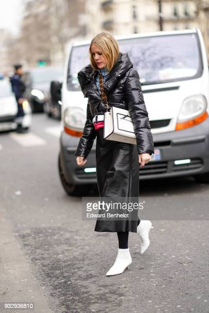 A guest wears a lustrous black puffy jacket with pink and white stripes a black leather long skirt white pointy toe kittenheeled booties a brown...