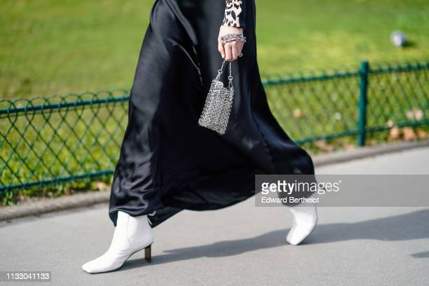 Guest wears a lustrous black satin flowing skirt, white boots, a small metal mesh bag, outside Paco Rabanne, during Paris Fashion Week Womenswear...