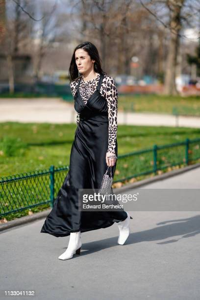 A guest wears a lustrous black satin flowing strappy dress a leopard print top white boots a small metal mesh bag outside Paco Rabanne during Paris...