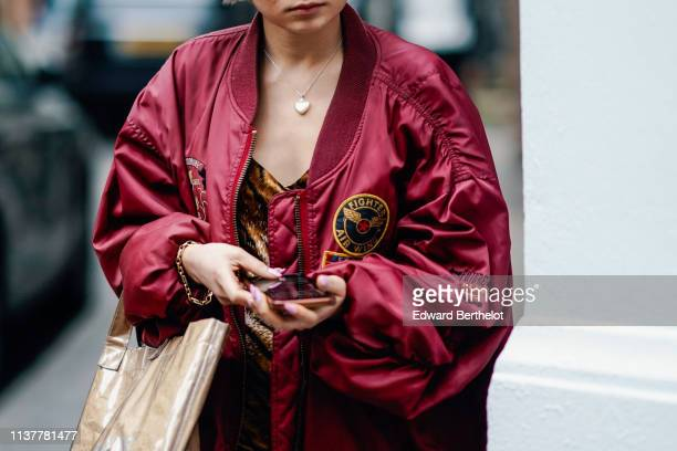 A guest wears a lustrous burgundy bomber jacket during London Fashion Week February 2019 on February 16 2019 in London England
