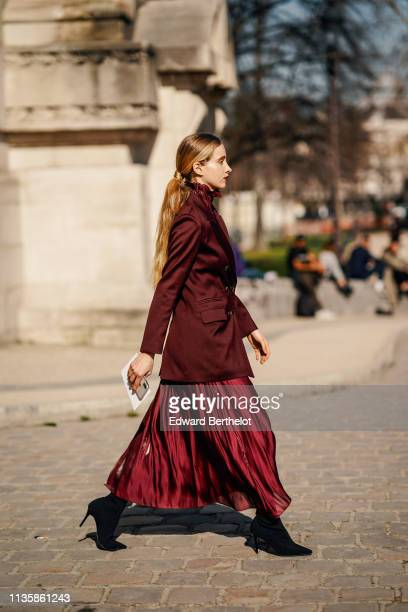 A guest wears a lustrous burgundy jacket a shiny highneck gathered flowing burgundy dress black pointy heeled boot soutside Maison Margiela during...