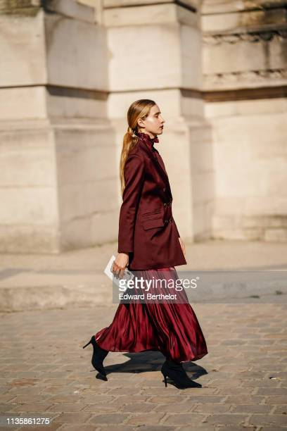 Guest wears a lustrous burgundy jacket, a shiny high-neck gathered flowing burgundy dress, black pointy heeled boot, soutside Maison Margiela, during...