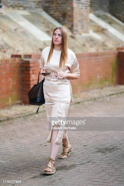 Guest wears a lustrous cream-color dress, a black bag, rope platform gladiator sandals, during London Fashion Week September 2019 on September 15,...