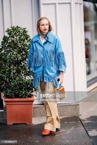 A guest wears a lustrous fringed blue leather jacket beige wideleg pants a brown alligator pattern handbag with a pearl handle orange studded shoes...