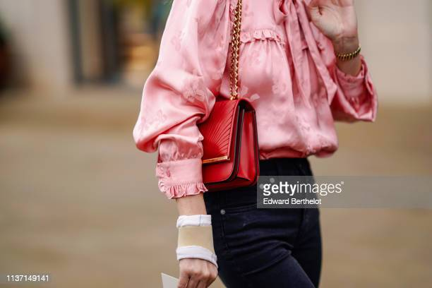 A guest wears a lustrous pink damask top with gathered cuffs and a bow a red bag during London Fashion Week February 2019 on February 16 2019 in...