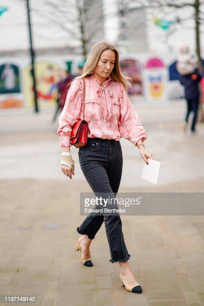 A guest wears a lustrous pink damask top with gathered cuffs collar and a bow a red bag black ripped hem flare pants beige and black Chanel sling...