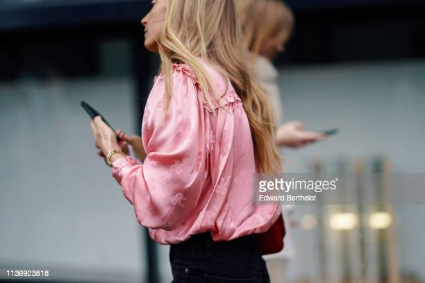 A guest wears a lustrous pink satin gathered top during London Fashion Week February 2019 on February 16 2019 in London England