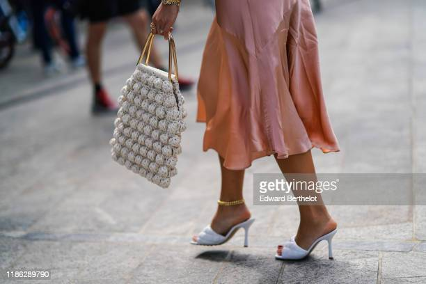 A guest wears a lustrous pink skirt an anklet white quilted heeled mules a white knit bag outside the Sportmax show during Milan Fashion Week...