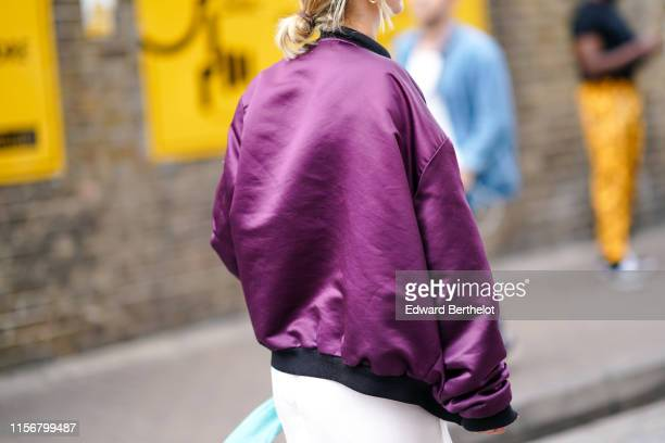 A guest wears a lustrous purple satin bomber jacket a white skirt during London Fashion Week Men's June 2019 on June 08 2019 in London England