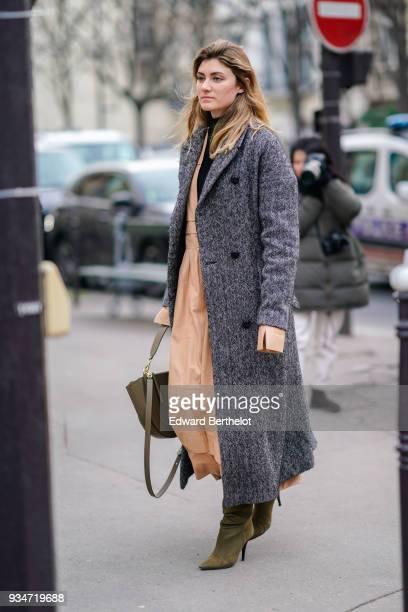 A guest wears a marled grey maxi coat a peach maxi dress a khaki handbag khaki suede pointy toe highheeled boots during Paris Fashion Week Womenswear...