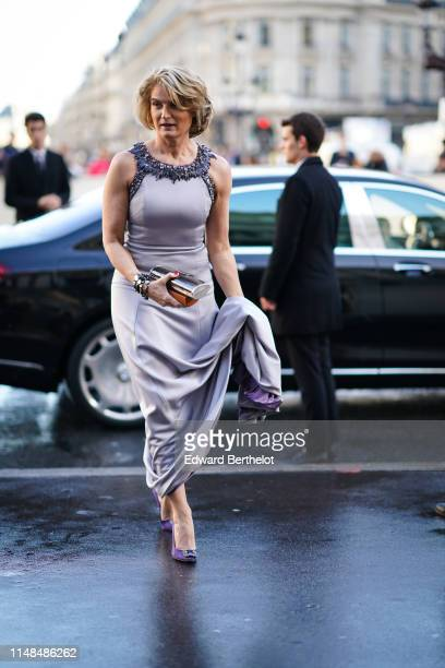 Guest wears a mauve long dress with a bejewelled collar, purple bejewelled pumps, bracelets, a shiny silver minaudiere, outside the Opera Garnier...