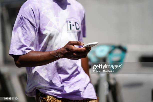 A guest wears a mauve tieanddye tshirt with the inscription iD bracelets brown and black leopard print short pants outside Bode during Paris Fashion...