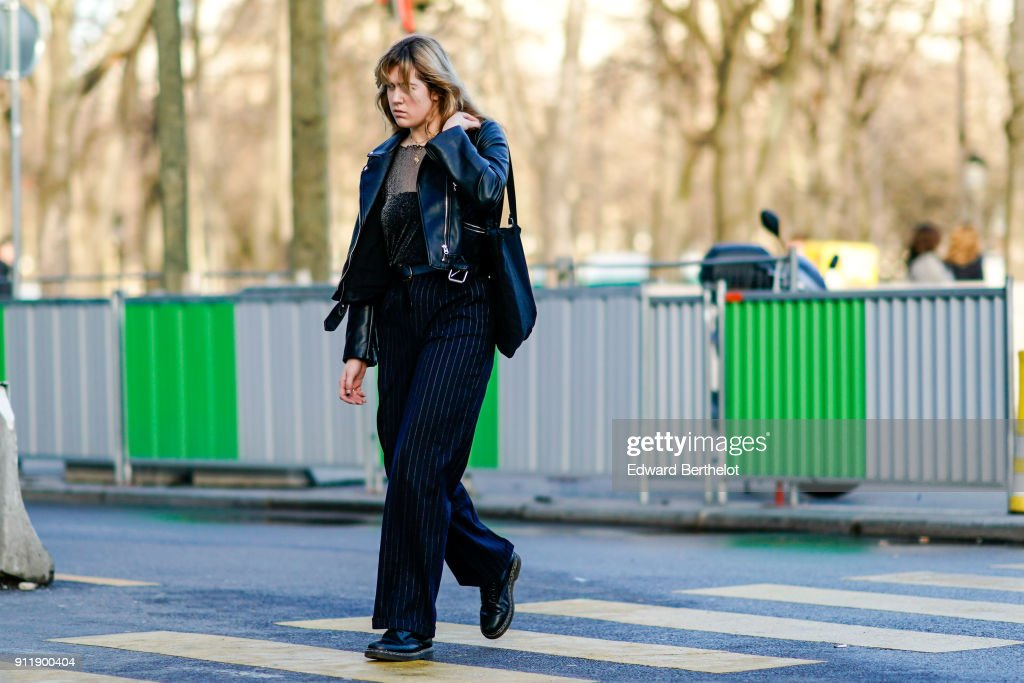 A guest wears a mesh top, a black leather jacket, pants, outside Chanel, during Paris Fashion Week -Haute Couture Spring/Summer 2018, on January 23, 2018 in Paris, France.