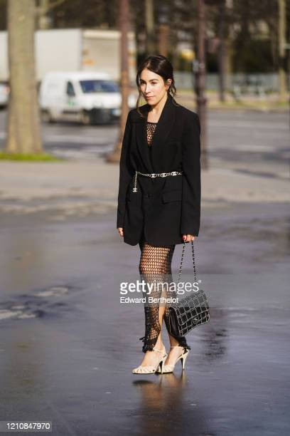 Guest wears a mesh top, a black oversized blazer jacket, a Chanel belt, fishnet skirt, a bag, pointy shoes, outside Chanel, during Paris Fashion Week...