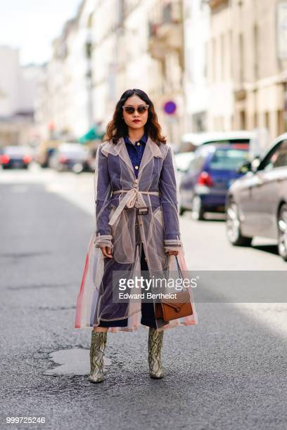 A guest wears a mesh trench coat snake print boots a brown bag outside Wooyoungmi during Paris Fashion Week Menswear SpringSummer 2019 on June 23...