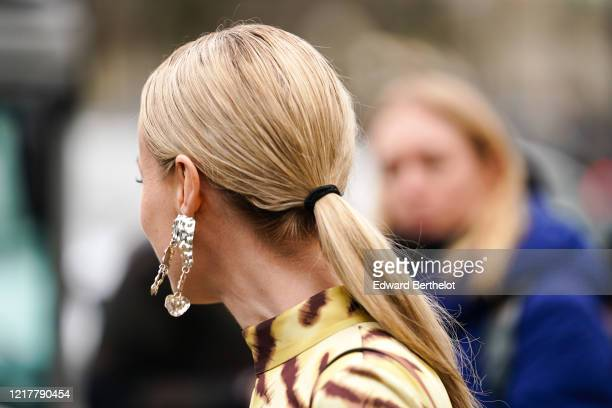 A guest wears a metallic silver long earring outside Ann Demeulemeester during Paris Fashion Week Womenswear Fall/Winter 2020/2021 on February 27...