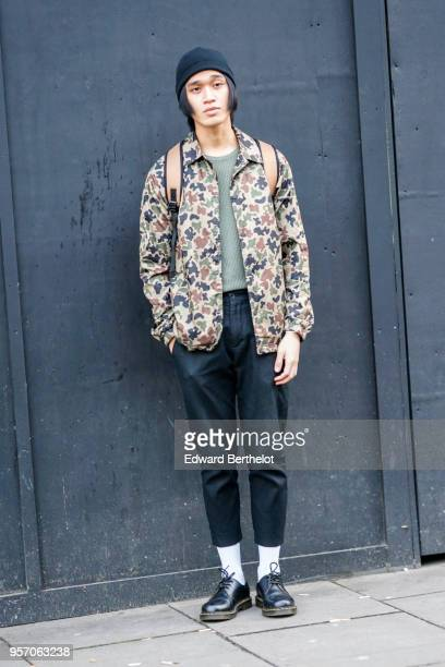 A guest wears a military camo print jacket cropped pants white socks black leather shoes a beanie hat during London Fashion Week Men's January 2018...