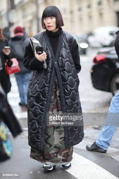 A guest wears a military camouflage print dress and a black long puffer coat outside the Veronique Branquinho show during Paris Fashion Week...