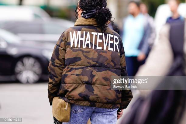 A guest wears a military camouflage print puffer jacket with printed word whatever outside Chanel during Paris Fashion Week Womenswear Spring/Summer...