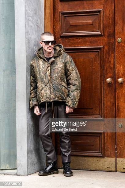 A guest wears a military camouflage puffer jacket black pants black leather shoes sunglasses during London Fashion Week Men's January 2019 on January...