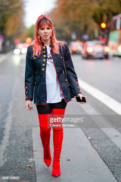 A guest wears a military jacket with golden buttons red thigh high boots has red pink hair outside John Galliano during Paris Fashion Week Womenswear...