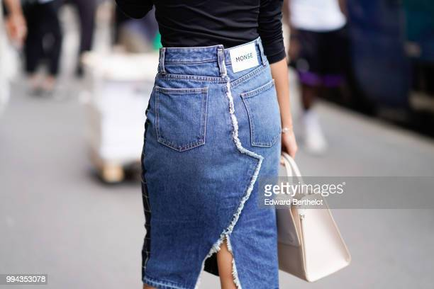 A guest wears a Monse blue denim skirt outside Elie Saab during Paris Fashion Week Haute Couture Fall Winter 2018/2019 on July 4 2018 in Paris France