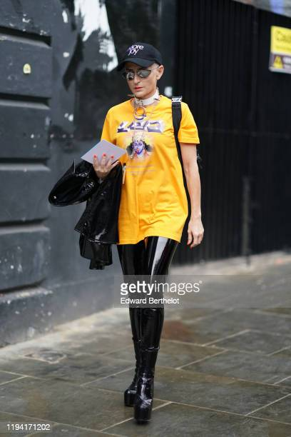 """Guest wears a """"More Joy"""" cap, a choker with spikes, mirror sunglasses, a yellow t-shirt with a printed purple face and the inscription """"Elevate your..."""